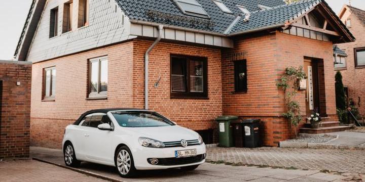 roedt murstens hus i to etager med hvid bil